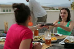 Female friends with tablet computer celebrating dinner on the terrace C Stock Footage