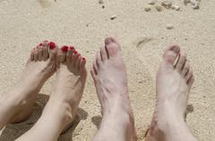 Two pairs of feet as a couple relax on the beach in Okinawa Stock Photos