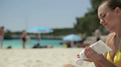 Woman on the beach applying sun block lotion on her arm, tracking shot HD Stock Footage