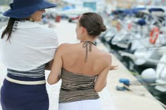 Two women talking and walking along marina, slow motion, steadycam shot - stock footage