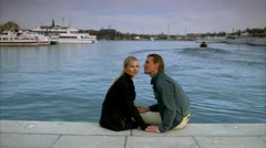 Scandinavian couple sitting by the sea, man leaning forward whispering Stock Footage