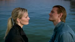 Scandinavian couple sitting by the sea, man leaning forward whispering in the Stock Footage