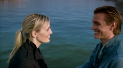 Scandinavian couple sitting by the sea, woman leaning forward whispering in the Stock Footage