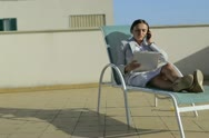 Businesswoman with cellphone and dokuments on sunbed, outdoor Stock Footage