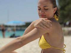 Woman on the beach applying sun block lotion on her arm, tracking shot NTSC Stock Footage
