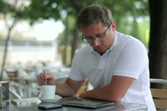 Young man working on tablet computer in cafe, outdoor Stock Footage