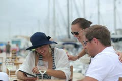 Three friends chatting on tablet computer at marina, steadycam shot Stock Footage