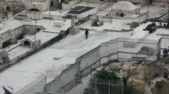 Judean man is walking on the roofs of Jerusalem Stock Footage