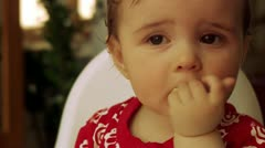 Girl sitting in a high chair eating biscuits Stock Footage