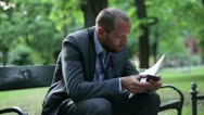 Just fired, unemployed businessman looking for job in newspaper Stock Footage