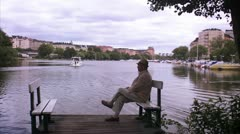 An elderly man sitting on a jetty, Stockholm Stock Footage