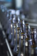 Empty beer bottles waiting to be filled on a productionline. Stock Photos