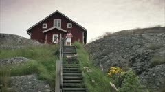 A woman walking down the stairs outdoors, Huvudskar, Stockholm archipelago Stock Footage