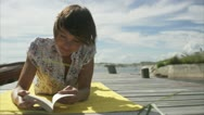 Stock Video Footage of A woman reading a book on a jetty, Huvudskar, Stockholm archipelago