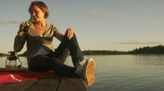 A young woman sitting on a jetty drinking beer, Blido, Stockholm archipelago Stock Footage