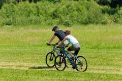 sport mountain couple biking downhill sunny meadows - stock photo