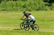 Sport mountain couple biking downhill sunny meadows Stock Photos