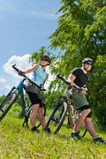 sport mountain biking couple relax in meadows - stock photo