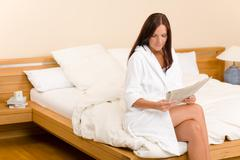 attractive woman read morning newspapers bedroom - stock photo