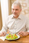 senior mature man eat vegetable salad - stock photo