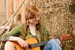 Young country woman playing guitar in barn Stock Photos