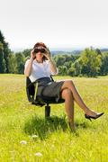 Businesswoman sit in sunny meadow seek binocular Stock Photos