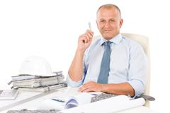 professional architect with blueprint behind table - stock photo