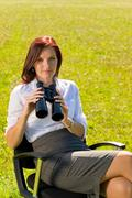businesswoman sit in sunny meadow seek binocular - stock photo