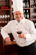 chef cook hold wine glass in restaurant - stock photo