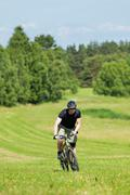 Sportive man mountain biking uphill sunny meadows Stock Photos
