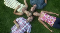 Four people lying on a lawn Stock Footage