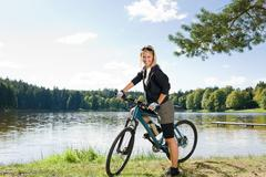 Mountain biking young woman relax by lake Stock Photos
