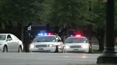 Two police cars in Washington DC, cops doing a traffic control Stock Footage