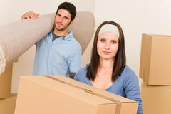 home moving young couple boxes and carpet - stock photo
