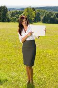 businesswoman sunny meadow point at empty banner - stock photo