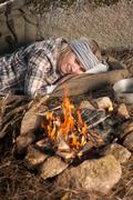 hiking woman with backpack sleep by campfire - stock photo