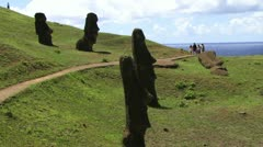 People walking through the Moai Statues at Easter Island Stock Footage