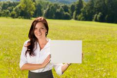 Stock Photo of businesswoman sunny meadow hold empty banner