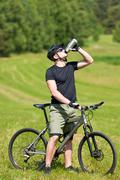 Sportive man mountain biking relax sunny meadows Stock Photos