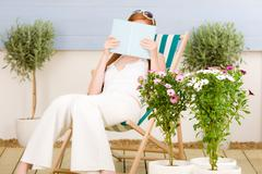 Summer terrace red hair woman read in deckchair Stock Photos