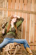 provocative young cowgirl drink beer in barn - stock photo