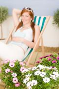Summer terrace red hair woman relax in deckchair Stock Photos