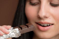 Chocolate - close-up woman bite sweets Stock Photos
