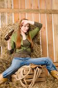 Provocative young cowgirl drink beer in barn Stock Photos