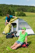Camping couple build-up tent sunny countryside Stock Photos