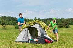 Stock Photo of camping couple build-up tent sunny countryside