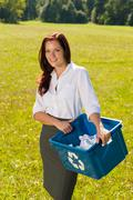 Stock Photo of recycling paper box businesswoman in sunny meadow