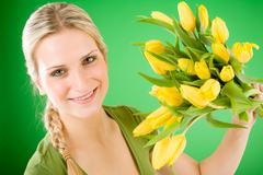 Stock Photo of young happy woman hold yellow tulips flower