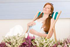 summer terrace red hair woman relax in deckchair - stock photo
