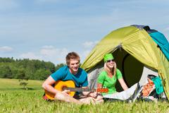 Stock Photo of camping couple playing guitar by tent countryside